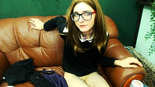 Nerdy young shemale in uniform pleases herself on the couch