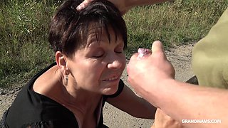 Perverted short haired mature brunette stands on knees to give BJ outdoors
